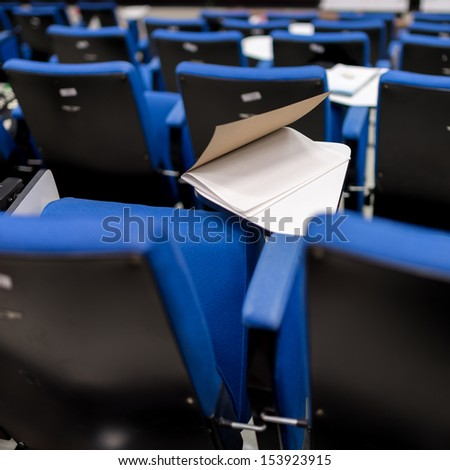 Book on the table of lecture chair in conferences room - stock photo