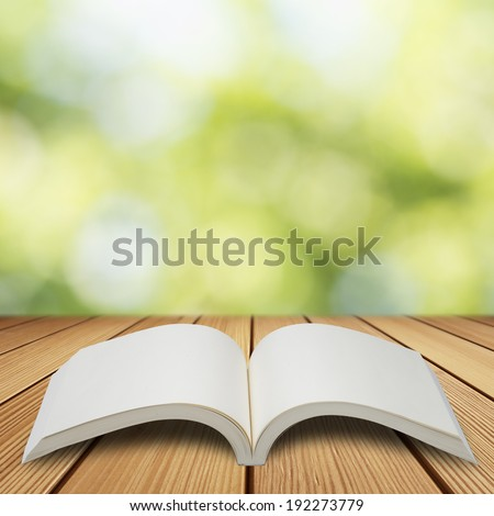 Book on wood table with summer scene background - stock photo