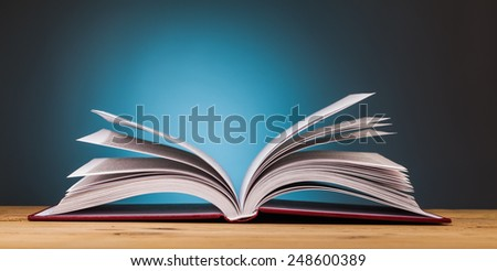 book on wooden table  with blue background - stock photo
