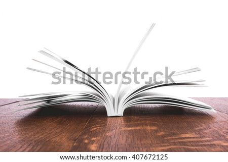 book, open, on old wooden table. - stock photo