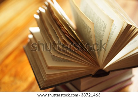 Book or bible on top of a stack of books on a wooden desk in library or classroom - stock photo
