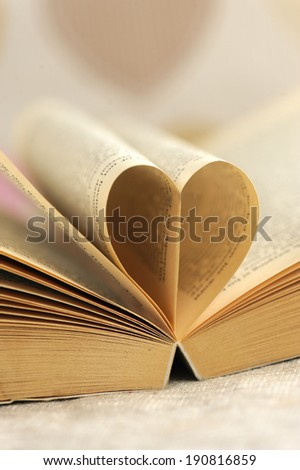 Book page in heart shape with heart pattern wallpaper atthe background - stock photo