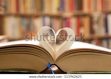 Book page in heart shape with library background - stock photo