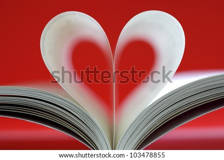 Book pages folded into heart shape on red background - stock photo