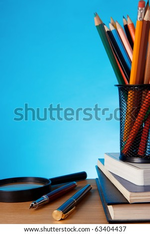 book, pen with pencil in holder basket and magnifying glass on table - stock photo