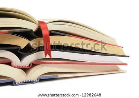 Book pile : small stack or heap of open books with red ribbon bookmark isolated on white background. - stock photo