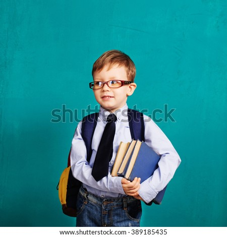 Book, school, kid. Diligent, sedulous, studious student holding books. Cheerful smiling little kid with big backpack against chalkboard. Looking at camera. School concept. Back to School - stock photo