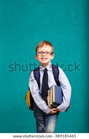 Book, school, kid. little student holding books. Cheerful smiling little kid with big backpack against chalkboard. Looking at camera. School concept. Back to School - stock photo