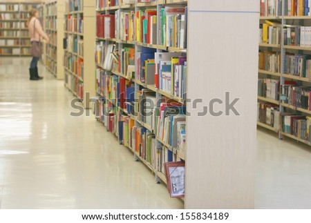Book shelves in public library, shallow DOF - stock photo