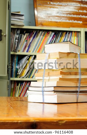 Book stack against book shelf in library - stock photo