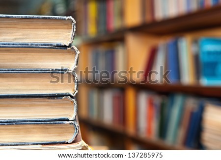 Book stack and book shelf in a library background - stock photo