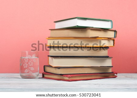 Book stacking. Open book, hardback books on wooden table and pink background. Back to school. Copy space for text