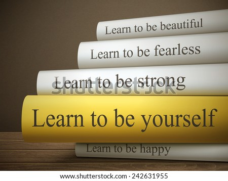 book title of learn to be yourself isolated on a wooden table over dark background - stock photo