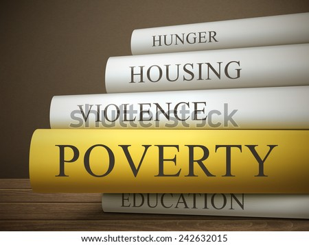 book title of poverty isolated on a wooden table over dark background - stock photo