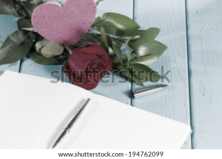 Book with a rose on top of an antique table in blue