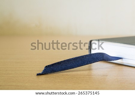 book with bookmark on wood table - stock photo
