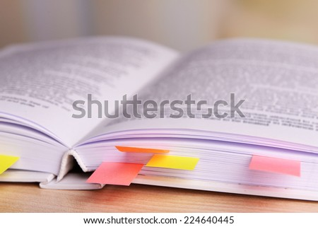 Book with bookmarks on table on bright background - stock photo