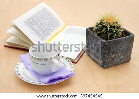 Book with cactus and a cup