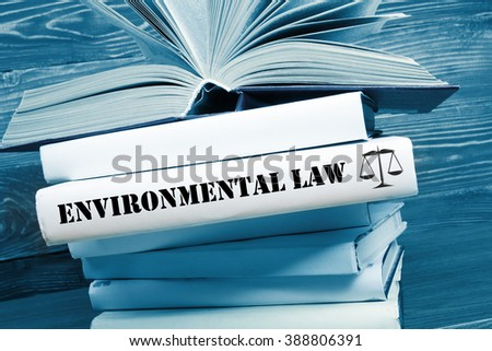 Book with Environmental Law word on table in a courtroom or enforcement office. Toned image - stock photo