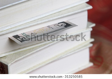 Book with five dollar bookmark, One dollar banknote used as book marker - stock photo