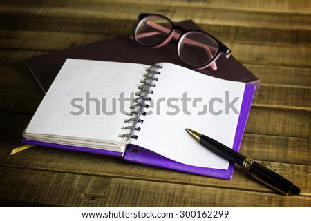 book with glasses and pen on the wooden background - stock photo