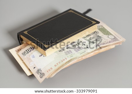 Book with Indian Currency Rupee bank notes on gray background - stock photo
