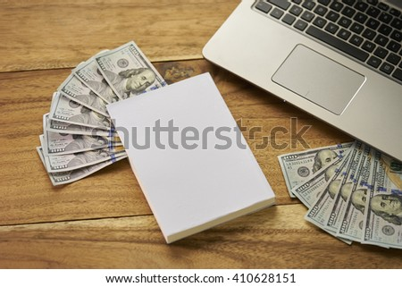 Book with money and Laptop - stock photo