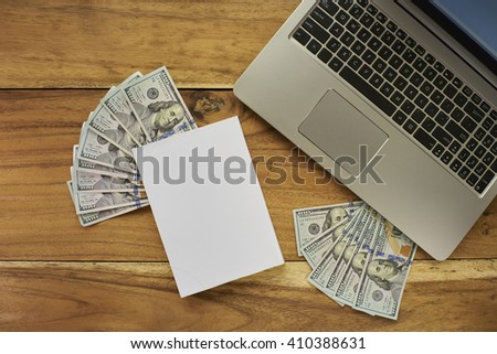Book with money and Laptop flat layout - stock photo