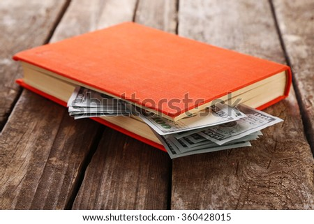 Book with nested dollar banknotes on wooden table. Stash of money - stock photo