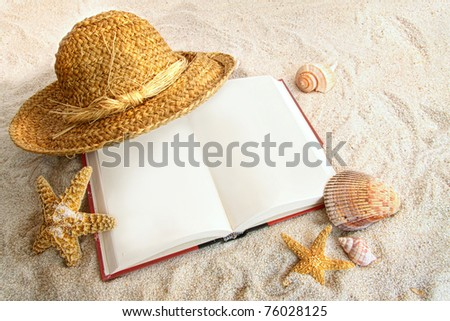 Book with straw hat and seashells at the beach - stock photo