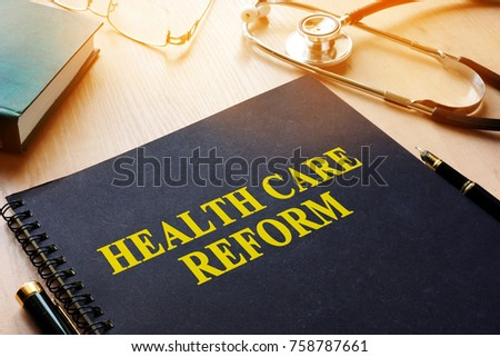 Book with title health care reform on a desk.