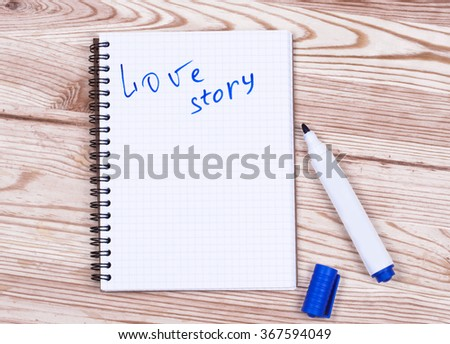 Book writing love story  and pen on wood desk