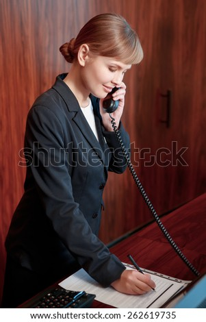Booking confirmed. Young attractive female receptionist answering the call and making notes at the notepad by the reception desk - stock photo