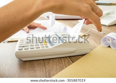 Bookkeeper doing calculations on an adding machine checking the totals against those in the journals, close up of her hands and the machine on a wooden desk. - stock photo