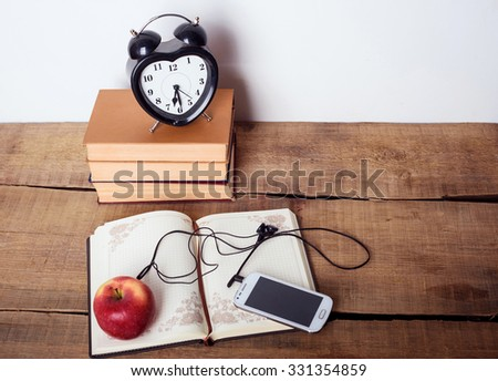 books, alarm clock, notepad, cellphone with earphones and apple on wooden background. Education equipment, education concept - stock photo