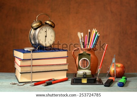 Books, Alarm Clock, school supplies and an apple on the table - stock photo