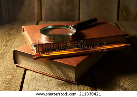 Books and a magnifier. On a wooden background. - stock photo