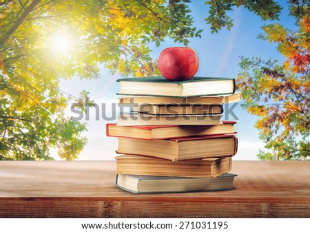Books and apple on the natural background - stock photo
