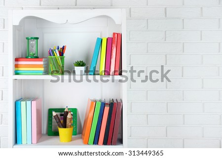 Books and decor on shelves in cupboard - stock photo