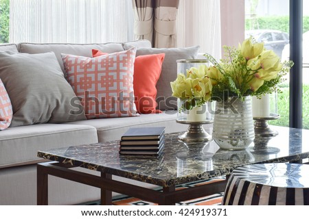 Books and decorative items on marble top table and lively sofa set  - stock photo