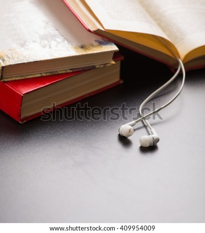 Books and ear plugs - stock photo