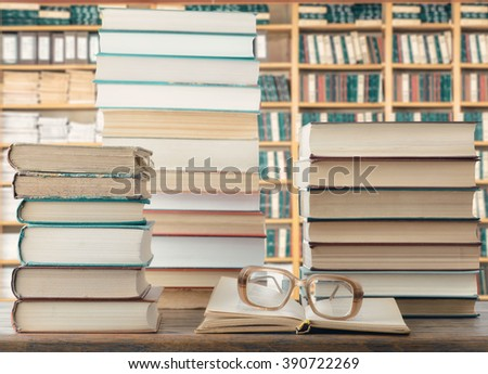 Books and eyeglasses In library - stock photo