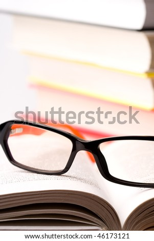books and glasses closeup on white background