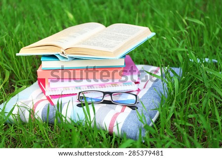 Books and glasses on pillow on grass close-up - stock photo