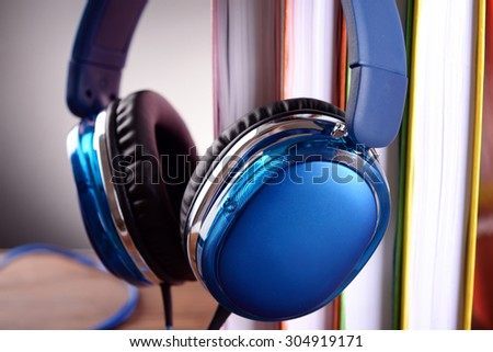 Books and headphones as audio books concept on grey background - stock photo
