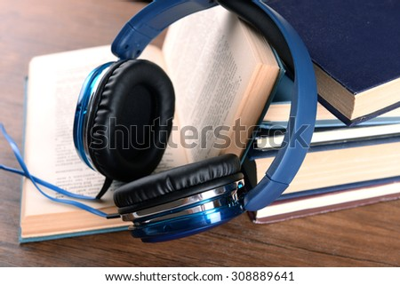 Books and headphones as audio books concept on wooden table, closeup - stock photo