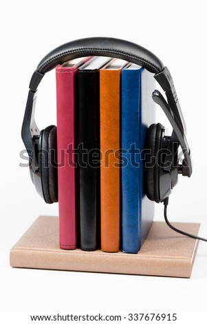 Books and headphones as audio books concept on wooden table on w