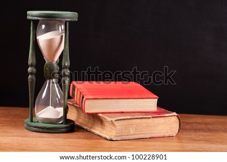 books and hourglass on table