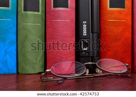 Books and laptop with many e-books inside - stock photo