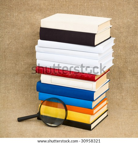 Books and magnifying glass on the fabric background - stock photo